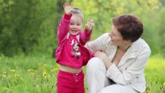 Little girl playing with her mother in garden look at camera. Middle shot Stock Footage