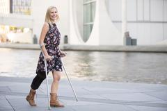 Blonde woman with crutches Stock Photos