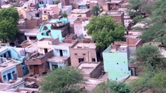 Buildings in village seen from above pan up to temple on hill Stock Footage