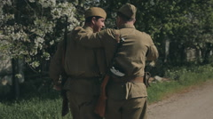 Two young soldiers coming with guns in uniforms on the road and communicate - stock footage