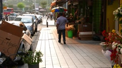 Indian man quickly come away on empty sidewalk passing flowers selling stand Stock Footage