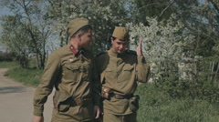 The lively conversation of two young men going to war in uniforms with guns Stock Footage