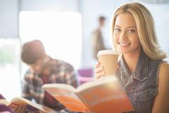 University student reading and drinking coffee - stock photo