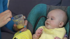 Babysitter give food in spoon to cute baby at home. 4K Stock Footage
