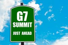 G7 SUMMIT Just Ahead written on green road sign  against clear blue sky - stock photo