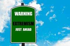 Warning EXTREMISM Just Ahead written on green road sign  against clear blue sky Stock Photos