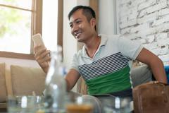 Asian Man Using Cell Phone Smile Sitting Cafe Stock Photos