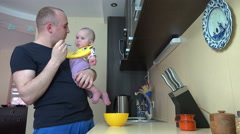 Father talk with baby daughter and feed with mash in spoon. 4K Stock Footage