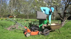 man unload cut grass into barrow. Lawn mowing in spring. 4K - stock footage