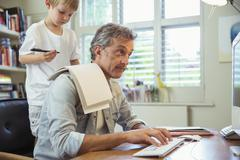 Son distracting father at work in home office - stock photo