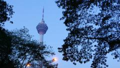 Fine view Kuala Lumpur Tower through dark leafage, against evening sky Stock Footage