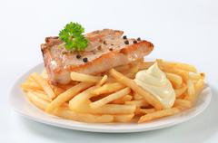 Pan seared pork chop with French fries and mayonnaise - stock photo