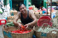 Asian man on street market smile sell red chilly pepper Stock Photos