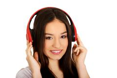 Rock woman with headphones listening to music. - stock photo