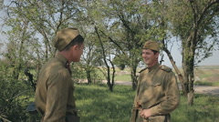 Conversation of two of young soldiers in a forest while smoking Stock Footage