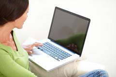 Relaxed caucasian woman in green shirt using a laptop while sitting - copy sp - stock photo