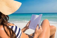 Pretty brunette reading on deck chair at the beach - stock photo