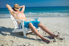 Man relaxing on deck chair at the beach - stock photo