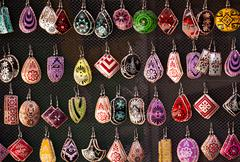 Many colorful handmade earrings for sale at outside street market - stock photo