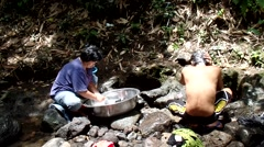 Man cleans and woman launders in river Stock Footage
