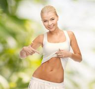 Beautiful sporty woman pointing at her abs Stock Photos