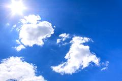 Clouds and sun on blue sky - stock photo