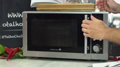 Food, Closing and switching on microwave oven - stock footage