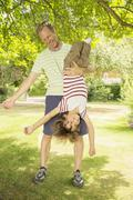 Father holding son upside-down in backyard Stock Photos