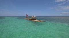 Man rowing a bamboo raft in the Caribbean Sea in Jamaica Stock Footage