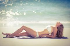 Lying pretty woman tanning on beach Stock Photos