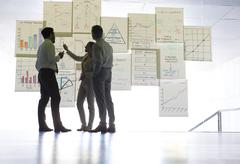 Business people discussing charts and graphs hanging in office Stock Photos