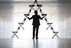 Businessman arranging office chair installation art - stock photo