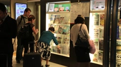 Tourists looking at brochure in information center of Kyoto train station Stock Footage