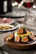 Honey Pouring Over Brie Cheese and Figs Stock Photos