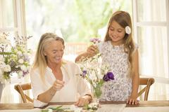 Grandmother and granddaughter arranging flowers - stock photo