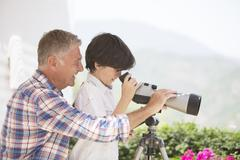 Grandfather and grandson using telescope - stock photo