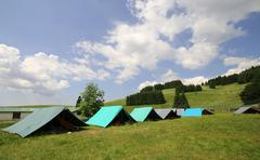 row of tents in the summer camp of the boyscout - stock photo