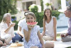 Girl eating watermelon at picnic Kuvituskuvat