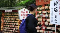 Woman looking at small ornamental wooden pieces at shrine of Arashiyama Stock Footage