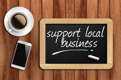 Coffee, phone and chalkboard with support local business words Stock Photos