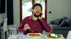 Happy man having fun eating spaghetti and joking on the phone at home - stock footage