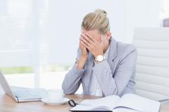 Frowning businesswoman grasping her head - stock photo