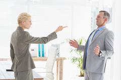 Businesswoman giving out to her boss - stock photo