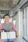 Portrait of happy casual businessman carrying box of belongings in office - stock photo