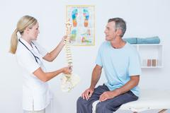 Stock Photo of Doctor showing anatomical spine to her patient