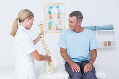 Doctor showing anatomical spine to her patient Stock Photos