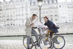 Men on bicycles reading map along Seine River, Paris, France - stock photo