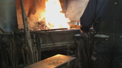 Blacksmith working In A Forge Furnace with lots of metal Stock Footage
