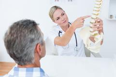 Stock Photo of Doctor explaining anatomical spine to her patient