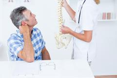 Doctor showing anatomical spine to her patient - stock photo
